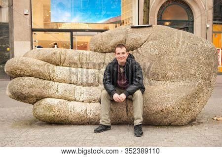 Young Caucasian Man Sitting On Huge Stone Hand On Street Of Antwerp, Belgium In Early Spring Day. An