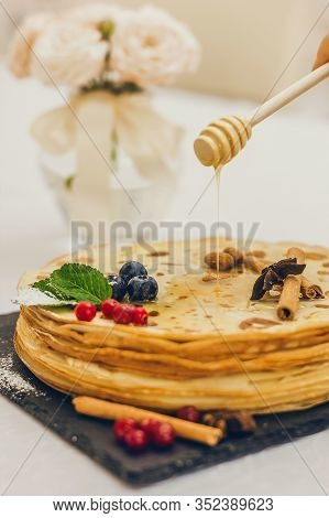Plate Of Pancakes Dripping With Caramel With Cranberries And Blueberries, Cinnamon Sticks. Shrovetid