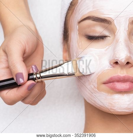 Beautiful young woman receiving facial mask at beauty salon