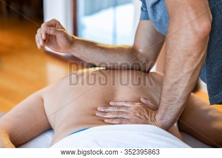 Sports Massage. A Young Sports Massage Therapist Applying Pressure With The Elbow. A Sportsman Recei