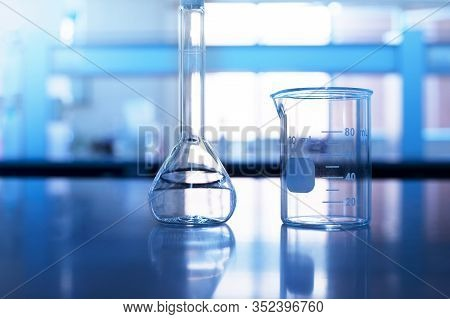 Beaker And Volumetric Flask On Chemistry Science Blue Laboratory Table Background