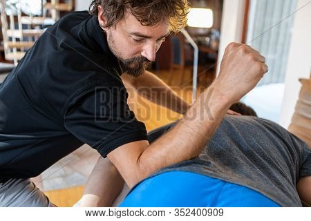 Professional Masseur Doing A Spine Massage On A Male Client Applying Pressure With His Forearm. A Sp