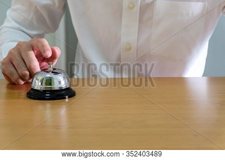 Men Wearing White Shirt Reaching His Hand And Finger To Ring A Reception Or Restaurant Bell On Wood