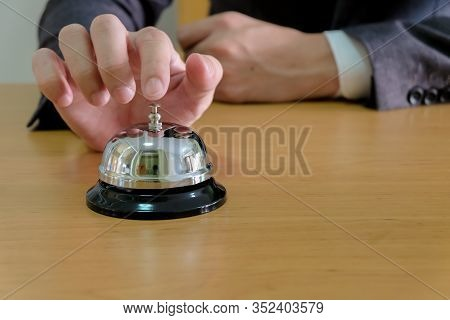 Men Business People With Suit Reaching His Hand And Finger To Ring A Reception Or Restuarant Bell On