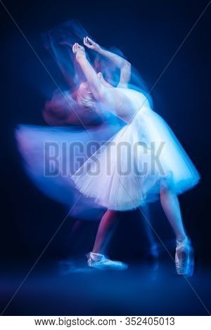 A full length portrait of a refined female ballet dancer posing in the studio over the dark blue background. Talent, fashion for ballet dancers.