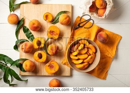 Peaches Whole Fruits With Leaves, Peaches In Halves, Peach Slices On A White Kitchen Table. The Proc