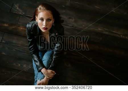 A portrait of a beautiful young woman sitting on the black floor. Beauty, cosmetics, evening makeup, women fashion.