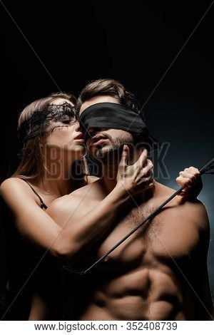 Dominant Woman Holding Flogging Whip Near Submissive And Blindfolded Man On Black