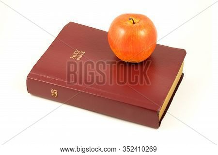 An Isolated Holy Bible And Red Apple Over A White Background.