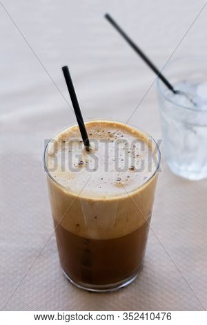 Cold Frappe Coffee With Ice Cubes On Glass With Black Straw Served On The Table In Caffeteria. Ice C