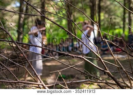 An Abstract View With Shallow Depth Of Field During A Qigong Tai Chi Demonstration, Two Women Are Se