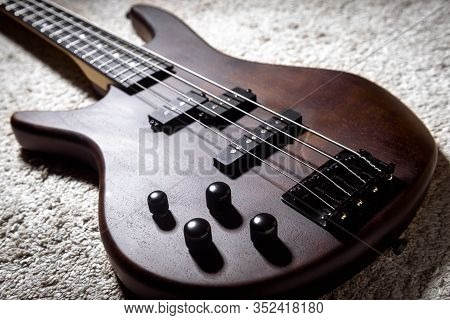Left-handed Bass Guitar With Four Strings. Popular Rock Musical Instrument. Close View Of Brown Elec