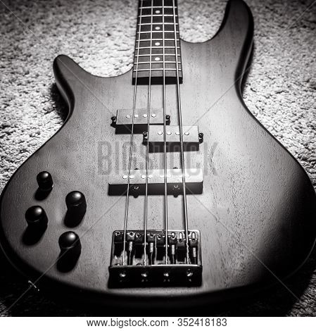 Left-handed Bass Electric Guitar With Four Strings In Black And White. Popular Rock Musical Instrume