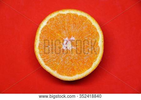 Half An Orange On A Red Background, Juicy Orange Fruit. Concept Of Healthy Food, Proper Nutrition, V