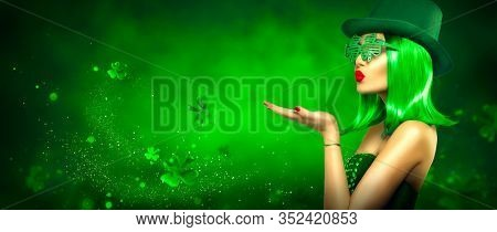 St. Patrick's Day leprechaun model girl pointing hand, holding product on green magic background, blowing flying shamrock leaves. Patrick Day pub party, celebrating. Border art design, Widescreen