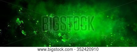 St. Patrick's Day abstract green background decorated with shamrock leaves. Patrick Day pub party celebrating. Abstract Border art design magic backdrop. Widescreen clovers on black with copy space.