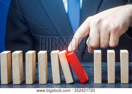 Businessman Starts The Process Of Falling Dominoes. Correction Of Errors Malfunctions. Implementatio