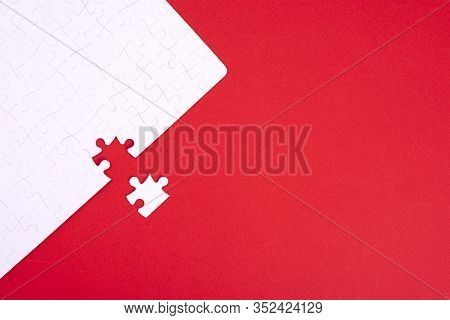 A Puzzle Of White Pieces With One Seized Element On A Red Background With Place For Your Text