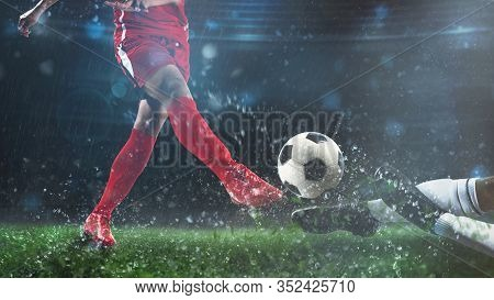 Football Scene At Night Match With Player In A Red Uniform Kicking The Ball And Opponent In Tackle T