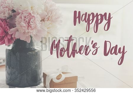 Happy Mother's Day Lettering On Pink And White Peonies In Vase And Gift Box With On Rustic Table In