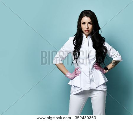 Serious-looking Brunette Woman Doctor, Nurse, Cosmetologist In Stylish Uniform And Medical Gloves Is