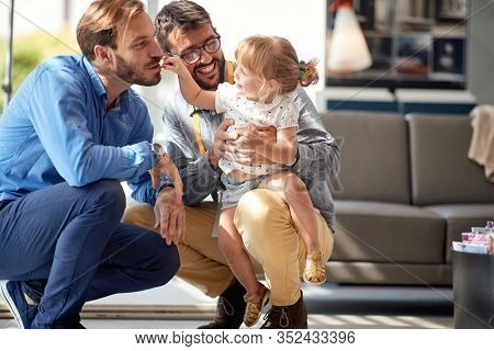 gay parents with child girl in store for household