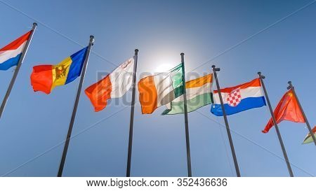 Colorful Flags Fluttering In The Wind Against Blue Sky. Summer Day, Sunny Daylight. Freedom, Politic