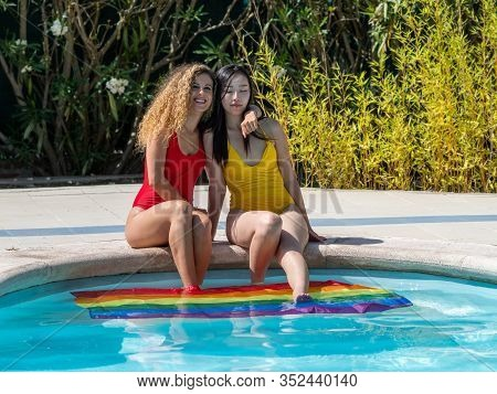 Stock Photo Of Two Girls Of Different Ethnicities Sitting At The Edge Of A Swimming Pool Embraced Wi