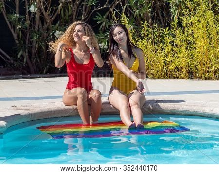 Stock Photo Of Two Girls Of Different Ethnicities Sitting At The Edge Of A Swimming Pool With An Lgt