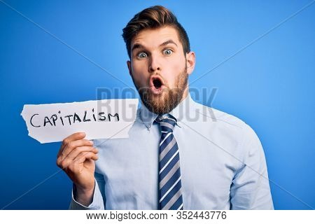 Young blond businessman with beard and blue eyes holding paper with capitalism message scared in shock with a surprise face, afraid and excited with fear expression