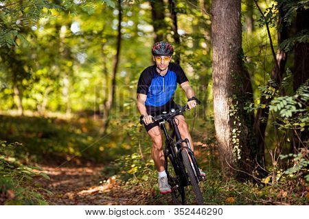 Young sporty Mountain-biker man practicing mountain biking in forest