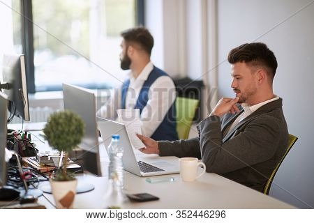 colleaugues at work. One is focused on work while other one is distracted and looking through window. focus, concentration, business concept