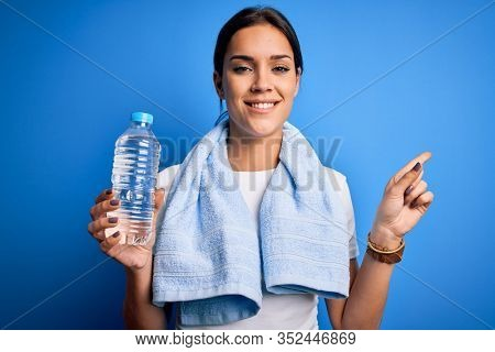 Young beautiful brunette sportswoman wearing towel drinking bottle of water to refreshment very happy pointing with hand and finger to the side