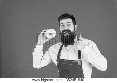 Bearded Well Groomed Man In Apron Selling Donuts. Donut Food. Hipster Baker Hold Donuts. Cheerful Mo