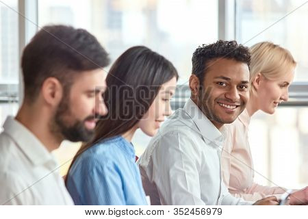 Indian Black Man Sitting Amoung Colleagues Smiling. Cheerful Black Man Working In Office With Co-wor