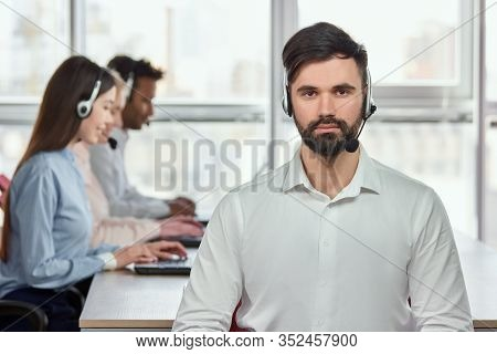 Portrait Of Handsome Sexy Bearded Call Center Operator. Caucasian Bearded Man Sitting In Office With