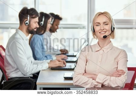Female Operator In Headset With Folded Hands. Blond Woman Worker In Call Center With Folded Hands Ag