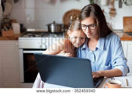 Mother And Daughter Using Laptop And Internet. Freelancer Workplace In Cozy Kitchen. Woman And Child