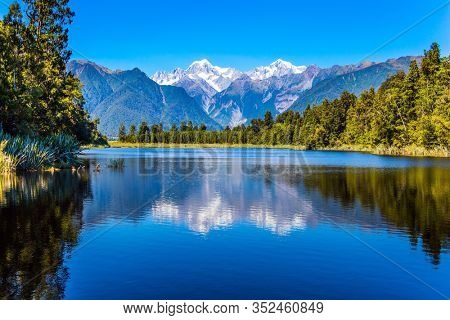 Magnificent snow-capped mountains surround the smooth, cold waters of Lake Matheson. The forests and  Mount Cook and Mount Tasman. The concept of ecological, active and photo tourism