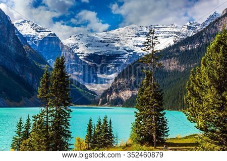 Sunny fine day. The lake with azure water is surrounded by mountains and forests. Glacial Lake Louise in Banff, Canadian Rockies. The concept of ecological, active and photo tourism