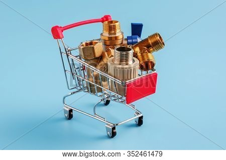 Red Shopping Cart With Plumbing Fittings Closeup. Brass Ball Valve, Y Filter, Tee And Polypropylene