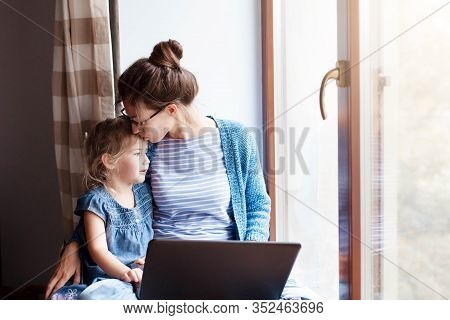 Mother Hug And Kiss Daughter. Working Mom Works From Home Office. Woman And Cute Child Sitting On Wi