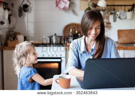 Working Mom Works From Home Office. Happy Mother And Daughter Smiling. Successful Woman And Cute Chi