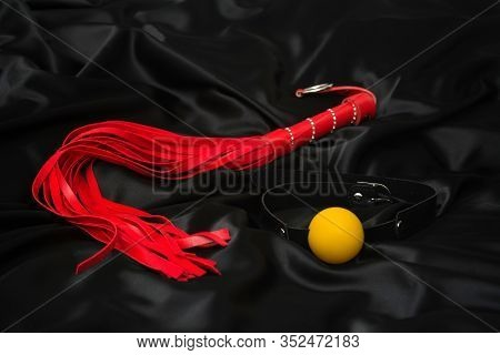 Red Whip And Gag On A Black Silk Background. Accessories For Adult Sexual Games.