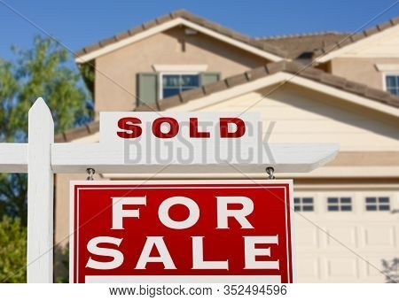 Sold Home For Sale Real Estate Sign and House.