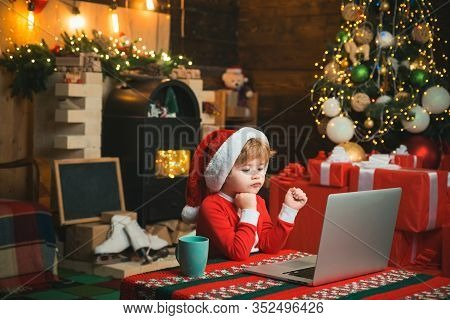 Christmas Little Boy Typing Letter To Santa Claus On A Computer At Home On Christmas Background. Lit