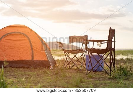 Camping Tents, Camp Tent And Chair By The River At Sunset In The Summer. Lifestyle Concept And Campi