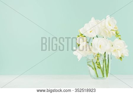 Fresh White Freesia Flowers In Cute Transparent Glass On Soft Light Green Mint Menthe Wall And White