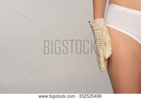 Partial View Of Slim Girl With Perfect Skin Holding Exfoliation Glove, Isolated On Grey