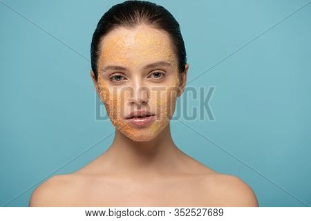 Beautiful Girl Applying Yellow Sugar Exfoliant On Face, Isolated On Blue